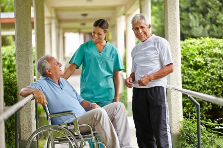 Two happy senior people taking to a nurse in a nursing home photo