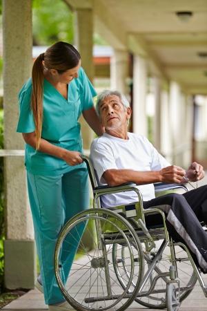enfermeria: Enfermera hablando con un anciano en silla de ruedas en un hogar de ancianos Foto de archivo