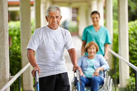 Happy senior people in nursing home with walker and wheelchair Stock Photo