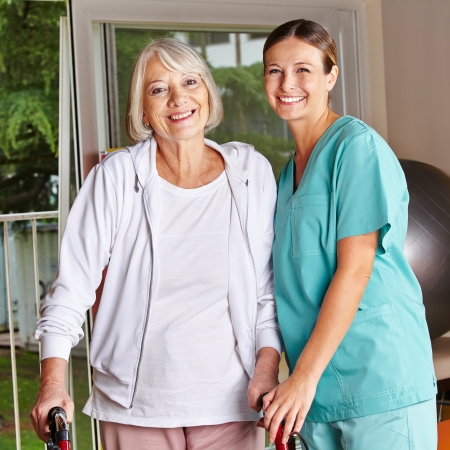 home health care: Happy senior woman with walker and nurse in a physiotherapy Stock Photo