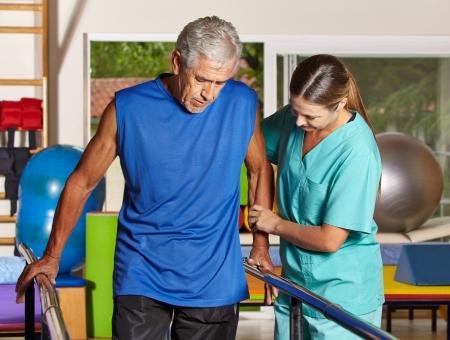 Senior man doet looptraining met fysiotherapeut in verpleeghuis