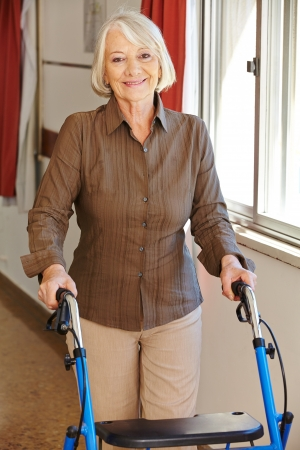 Senior woman walking with walker through a rest home photo
