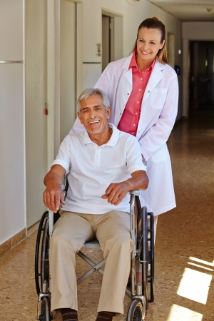 Geriatric nurse with senior man in wheelchair in a nursing home Stock Photo - 17660205