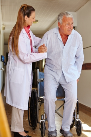 mobility nursing: Nurse in nursing home helping senior man in wheelchair with standing up Stock Photo