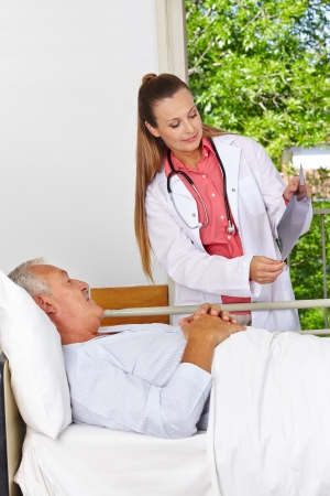 Doctor showing patient x-ray image at hospital bed Stock Photo - 17660302