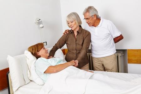 Personas mayores visitan mujer postrada en cama en cama de enfermo en un hospital
