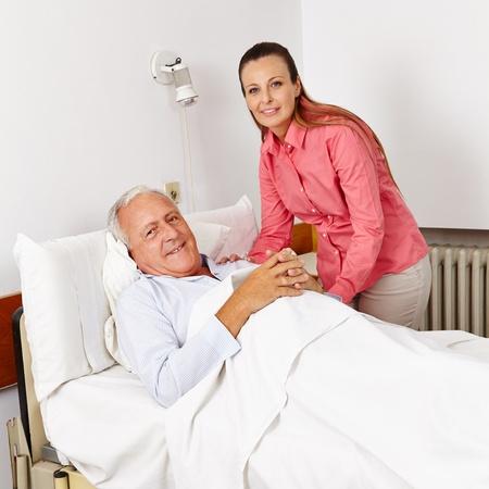 visitador medico: Mujer sonriente visitar hombre postrado en cama vieja en una cama de hospital