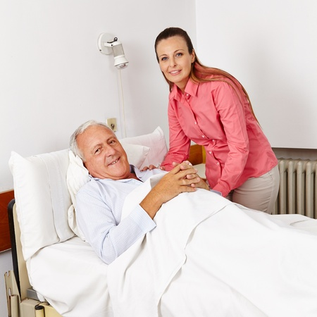 visit: Smiling woman visiting old bedridden man in a hospital bed Stock Photo