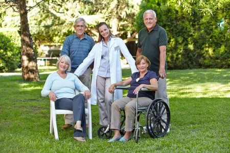 Group of senior people in retirement home garden with nurse photo