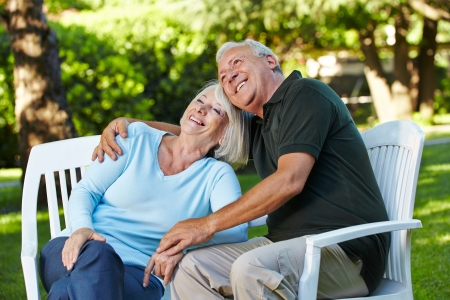 Happy senior couple sitting in a summer garden photo