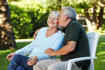 cheek: Senior man kissing his woman in a summer garden