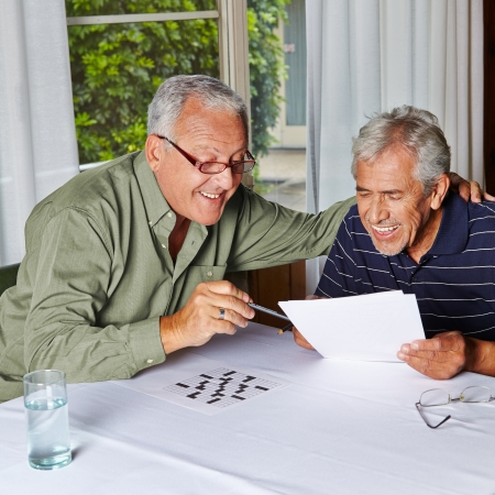 Two happy senior citizens solving riddles in a rest home photo