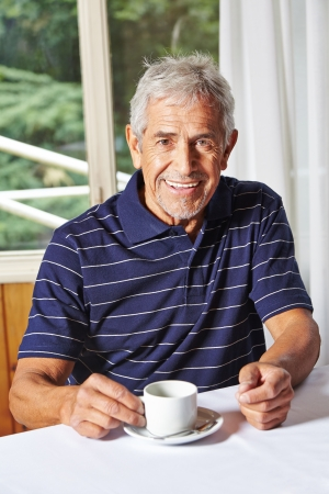 Happy senior man drinking a cup of coffee in a nursing home photo