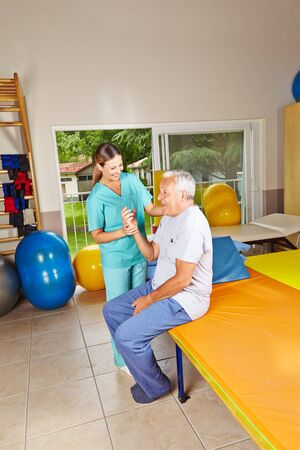 remedial: Senior doing remedial gymnastics in physiotherapy with nurse Stock Photo