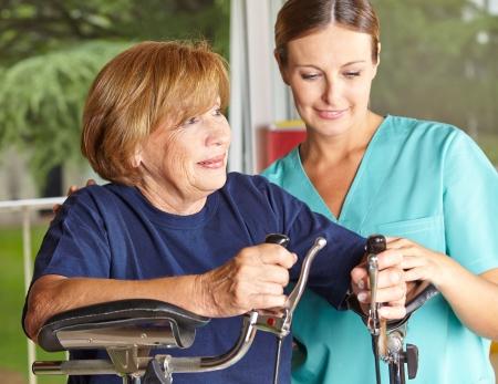 ergotherapie: Fysiotherapeut helpt senior vrouw op heilgymnastiek Stockfoto