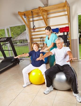 terapia ocupacional: Personas mayores haciendo gimnasia de rehabilitación en las pelotas de gimnasia