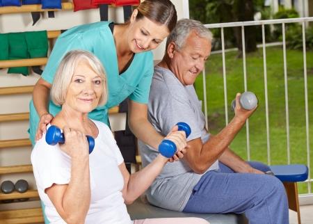 terapia ocupacional: Fisioterapeuta ayuda a las personas mayores con ejercicios con mancuernas
