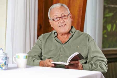nursing allowance: Senior man reading a book with reading glasses in a rest home Stock Photo