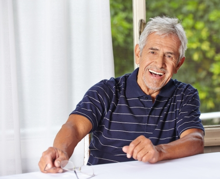 Happy smiling senior man sitting with reading glasses at a table photo