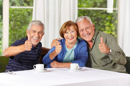 senior citizen woman: Happy senior people holding thumbs up while drinking coffee in retirement home