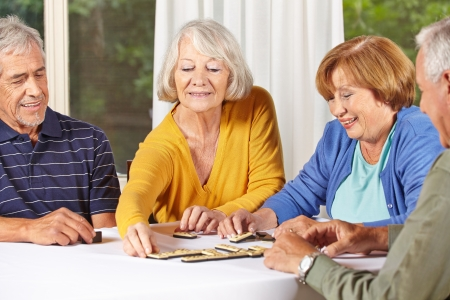 Group of senior people in retirement home playing domino game photo