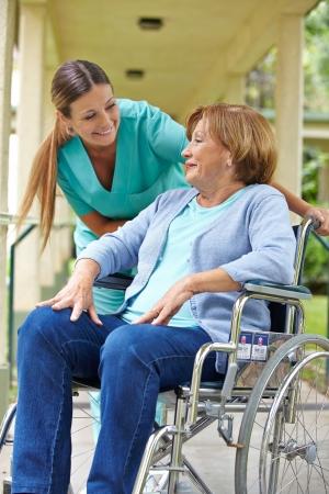 nursing treatment: Paciente anciano en silla de ruedas hablando con una enfermera en un hospital de jard�n Foto de archivo