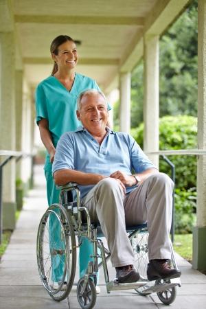 pielęgniarki: Starszy mężczyzna na wózku inwalidzkim z pielęgniarką w parku szpitala Zdjęcie Seryjne