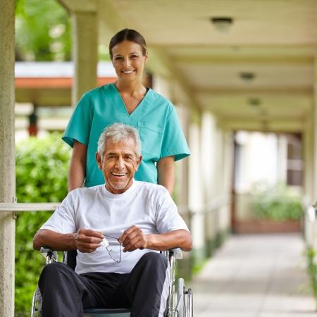 fysiotherapie: Senior man in rolstoel met verpleegster op een wandeling door de tuin van het ziekenhuis Stockfoto