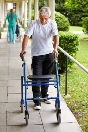 mobility nursing: Senior man on a walk with walker in the garden of a hospital