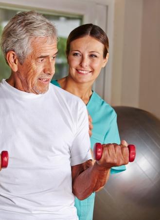 ergotherapie: Senior man doet afkickkliniek sporten in verpleeghuis met een fysiotherapeut Stockfoto