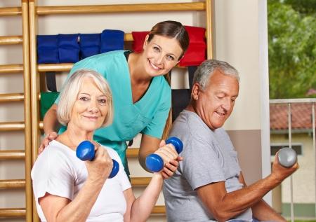 tercera edad: Dos personas mayores en el gimnasio haciendo ejercicios de gimnasio con pesas
