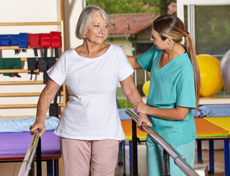 occupational therapy: Senior woman at kinesiotherapy with physiotherapist in nursing home Stock Photo