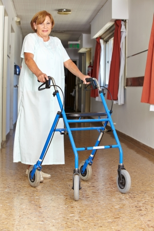 Senior woman walking with walker though a hospital photo