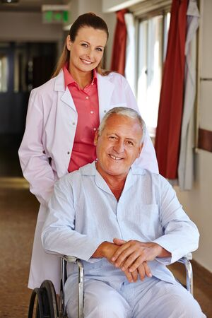 mobility nursing: Nurse with senior man in wheelchair in a hospital Stock Photo