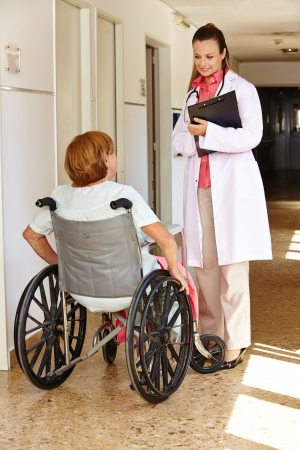 mobility nursing: Senior woman in wheelchair talking to nurse in a hospital