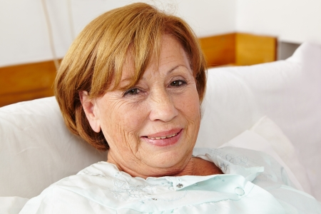 care allowance: Smiling senior woman sitting in bed in her sleeping room