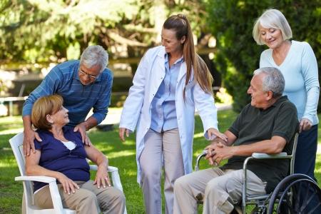 enfermeria: Muchas personas mayores se relajan en un parque de una casa de reposo con la enfermera geriátrica Foto de archivo