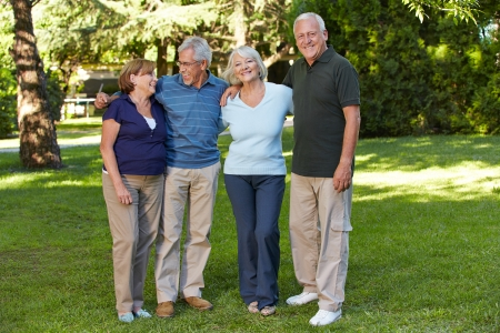 Two happy senior couples standing in the park of a retirement home photo