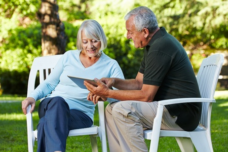 old pc: Two senior people sitting with a tablet PC in a nature park Stock Photo