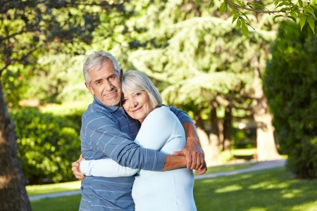Romantic happy senior husband and wife embracing in nature photo