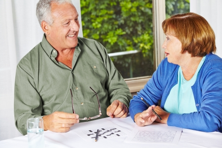 care allowance: Two seniors doing memory training with riddles in a rest home Stock Photo