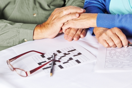 dementia: Two seniors holding their hands in a nursing home with riddles and glasses on table