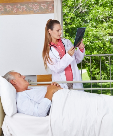 Radiologist looking at x-ray image with senior patient in a hospital Stock Photo - 17825191