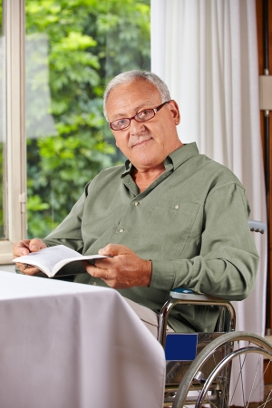 Senior man in wheelchair reading a book in a rest home photo