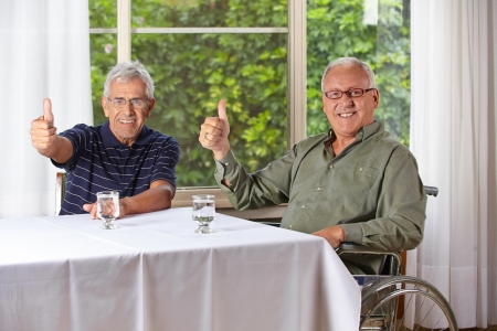 Two happy senior men in a rest home holding their thumbs up photo