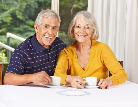 senior citizen woman: Happy senior couple drinking coffee in a retirement home Stock Photo