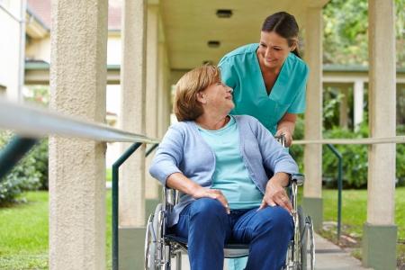 enfermeria: Mujer mayor en silla de ruedas hablando con una enfermera en un hospital de jardín