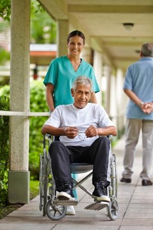 Happy nurse driving a senior man in wheelchair in a clinic Stock Photo - 17825181