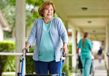 Old happy woman with walker on a stroll in the park of a nursing home photo
