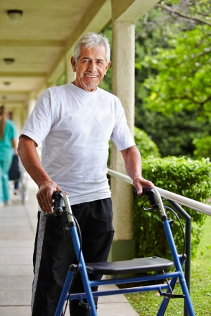 mobility nursing: Happy senior man walking with a walker in the park of a clinic